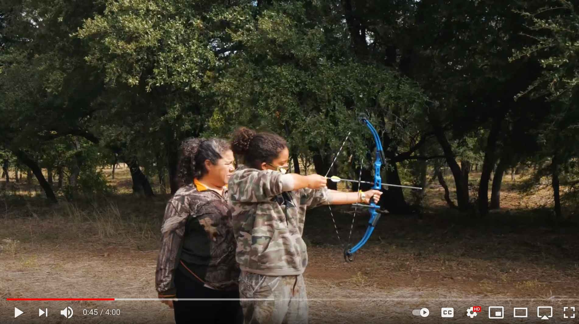 Young woman aiming a compound bow.